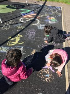 Kids drawing on the black tarmac ground with brightly coloured chalks